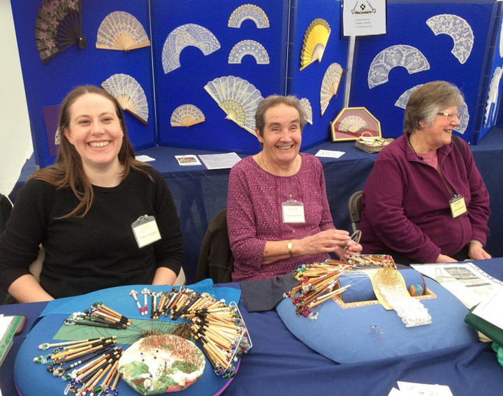 Three lacemakers demonstrating in front of the display of lace fans at Living crafts